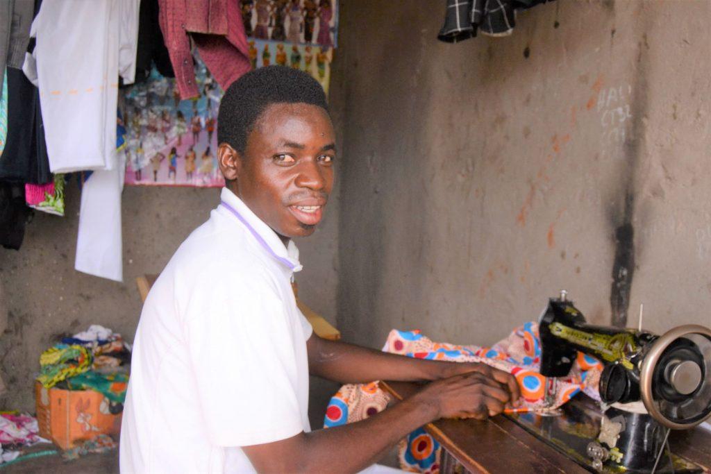 David dans son atelier de couture qu'il a ouvert grâce aux crédits reçus dans le groupe de microcrédit communautaire.