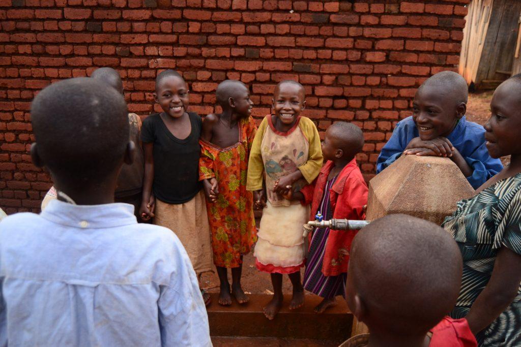 A Rukanda, des enfants en train de jouer autour d'une borne fontaine